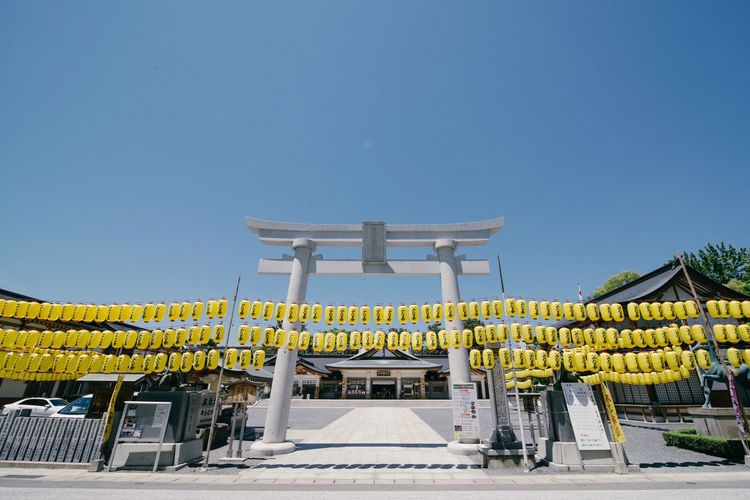 Yellow Lanterns At Entrance On Temple Against Clear Blue Sky