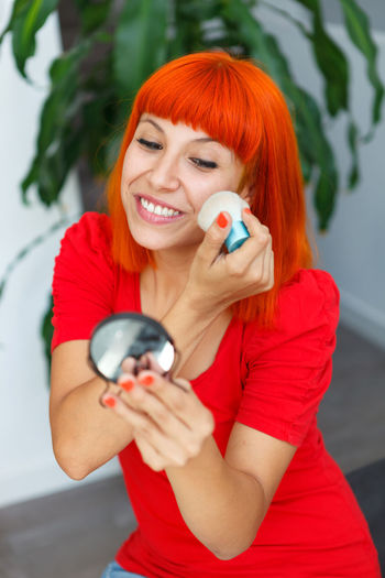 Smiling woman applying make-up while looking at hand mirror