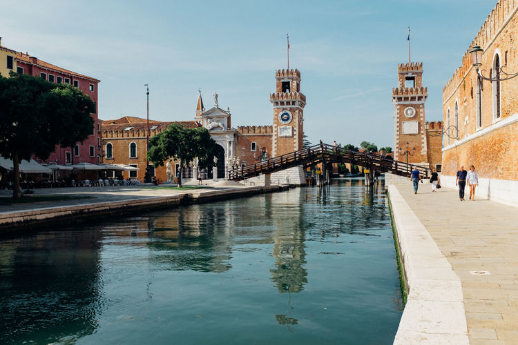 Canal and venetian arsenal against sky