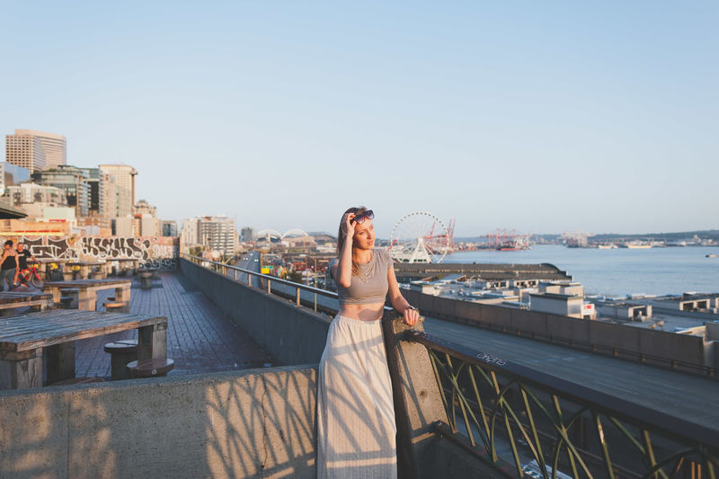 Beautiful woman standing at promenade against clear sky in city