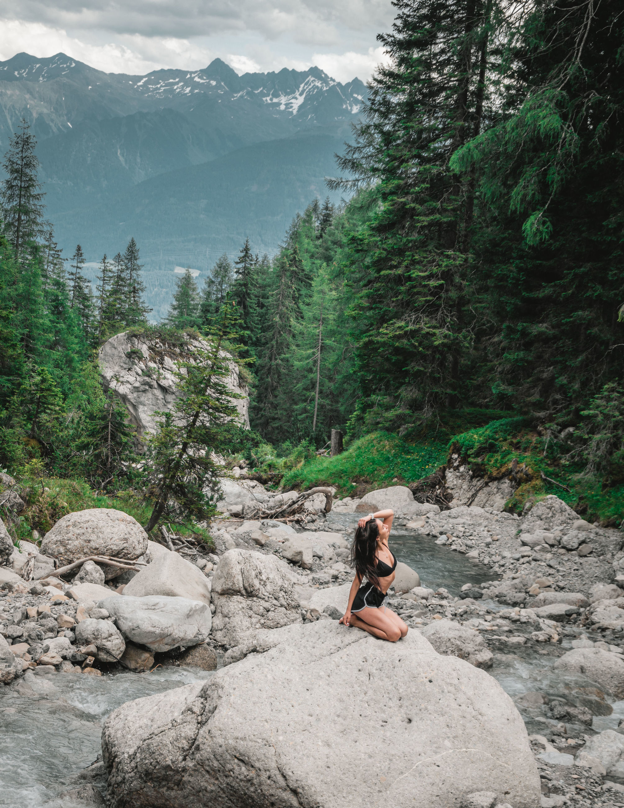 leisure activity, one person, mountain, sitting, tree, beauty in nature, nature, plant, adult, rock, lifestyles, scenics - nature, land, women, rock - object, full length, solid, mountain range, tranquility, outdoors