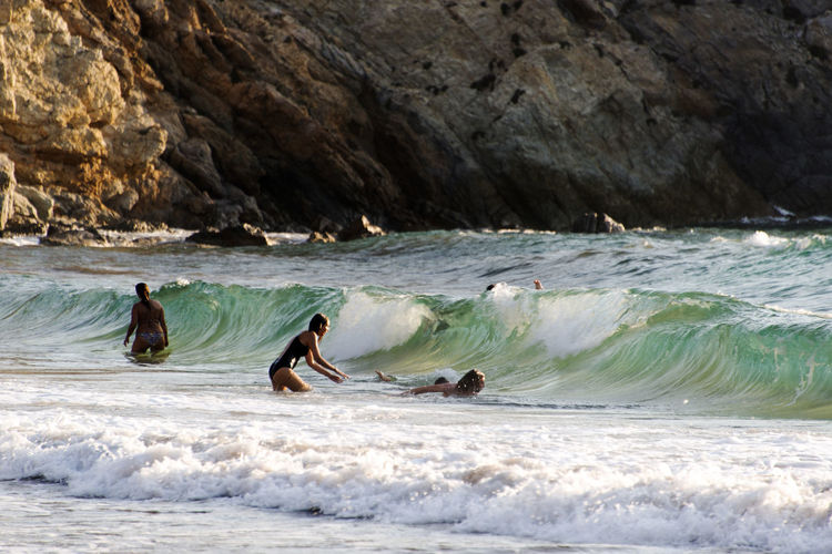 People playing, swimming in the waves in the island of Patmos, Greece in summer time Adventure Aquatic Sport Beauty In Nature Day Extreme Sports Leisure Activity Lifestyles Men Motion Nature Outdoors People Real People Sea Skill  Sport Surfing Water Waterfront Wave