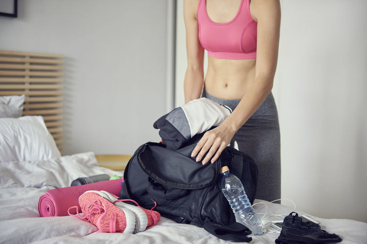 Midsection Of Woman Putting Cloth In Bag At Home