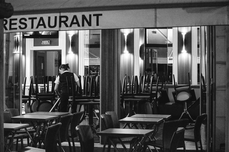 a woman cleans a restaurant at the evening Abend Black And White Calm Chair Cleaning Empty End Of The Day Evening Fegen Feierabend Lights Restaurant Schwarz Weiß Shadows Street Photography Streetphotography Woman Work