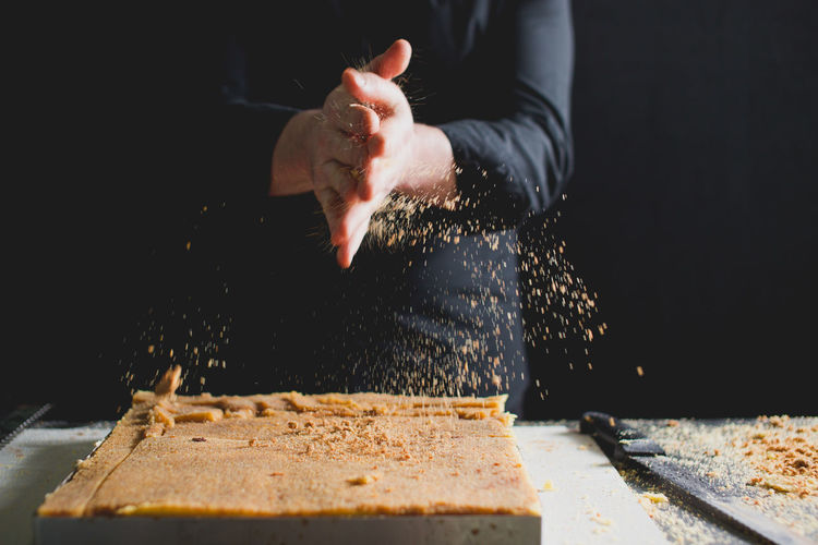CLOSE-UP OF CHEF'S HANDS PREPARING SPONGE CAKE