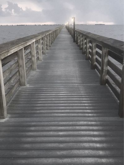 Empty wooden pier over sea against sky