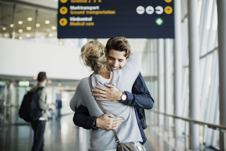 Happy businessman embracing colleague at airport