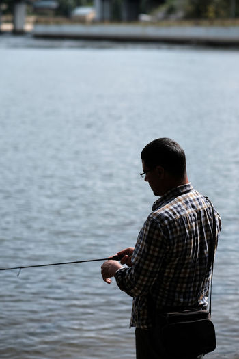 Rear view of man standing by lake and fishing