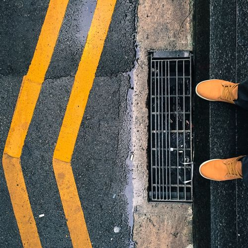 Low section of person wearing yellow shoes standing on footpath
