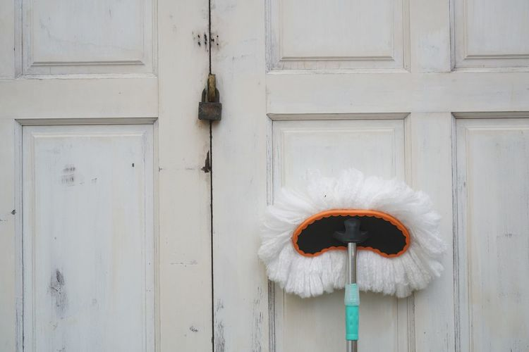 A white mop placed standing on the white vinatge door.