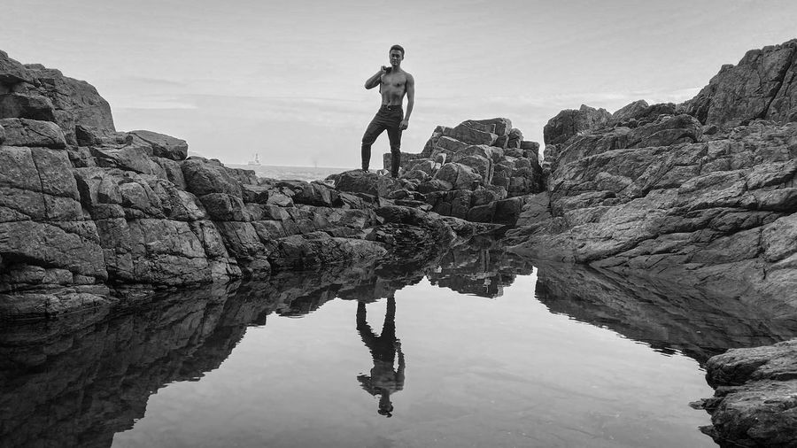 Man standing on rock by water