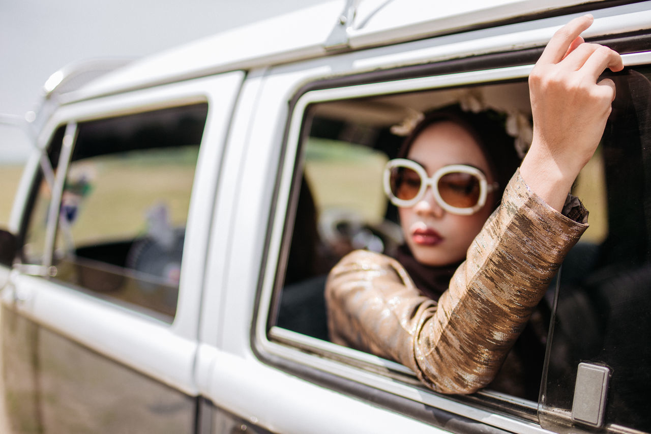 Adult Car Fashion Glasses Hairstyle Headshot Human Arm Land Vehicle Leisure Activity Lifestyles Mode Of Transportation Motor Vehicle One Person Outdoors Portrait Real People Sunglasses Transportation Travel Window Young Adult