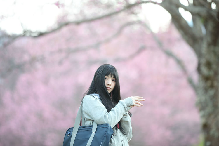 Woman standing by cherry tree