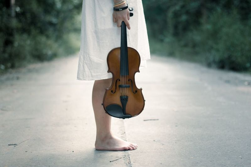 Low Section Of Woman With Violin Standing On Road