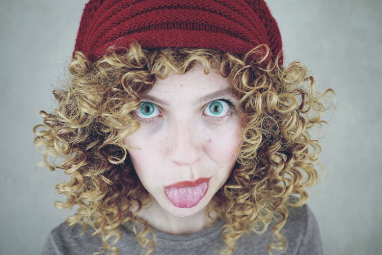Portrait of young woman sticking out tongue against gray background
