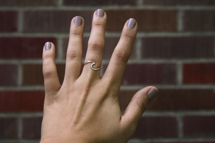 Cropped hand of woman wearing ring against brick wall