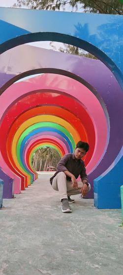 Full length of man standing at multi colored umbrella