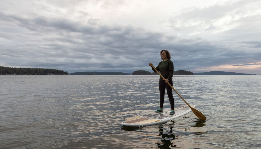 Full length of man standing in sea against sky
