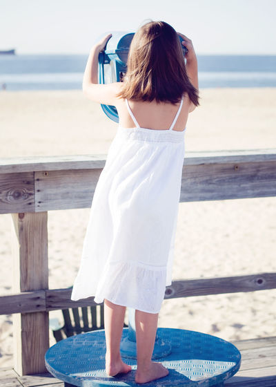 Rear view of girl looking through coin-operated binoculars at beach