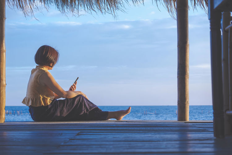 Woman using smart phone while sitting by sea