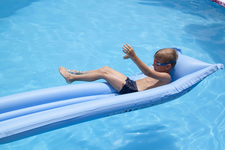 High angle view of boy relaxing in swimming pool