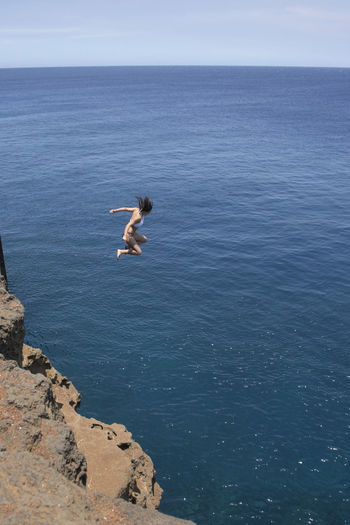 Woman Jumping Off Cliff In Sea