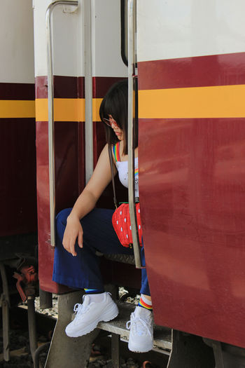 Young woman sitting at train entrance