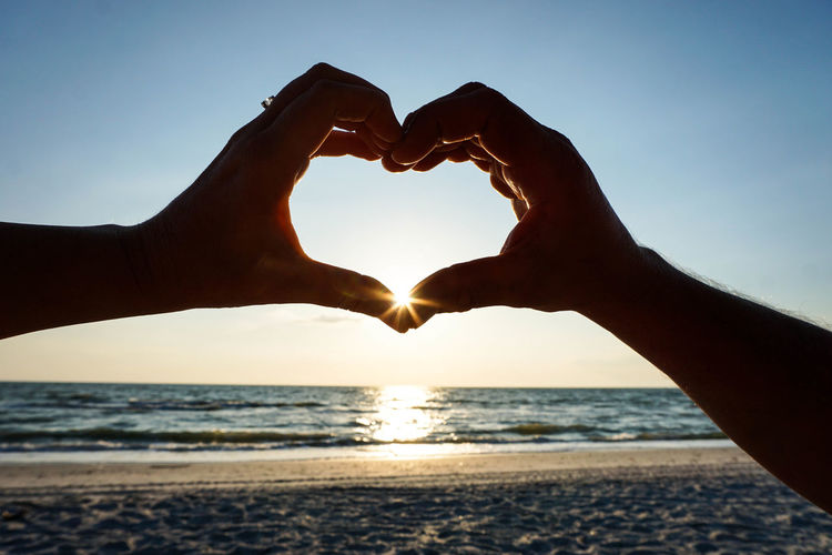 Hands in heart shape at sunset