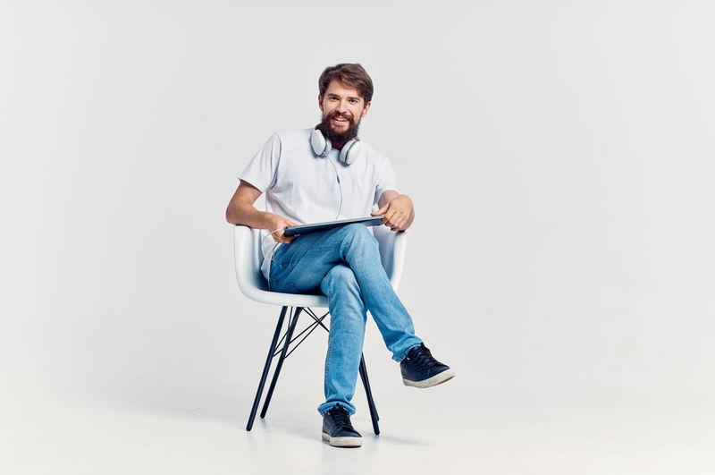 Portrait of young man sitting on chair against white background
