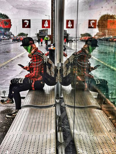 Rear view of men sitting on railing in city
