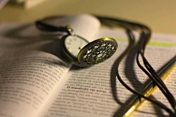 Close-up of pocket watch on open book