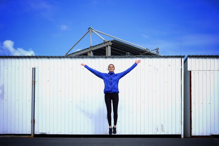 Portrait of woman jumping against blue sky
