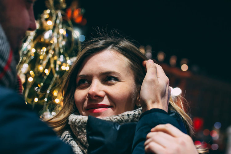 Portrait of smiling woman with illuminated christmas tree during winter