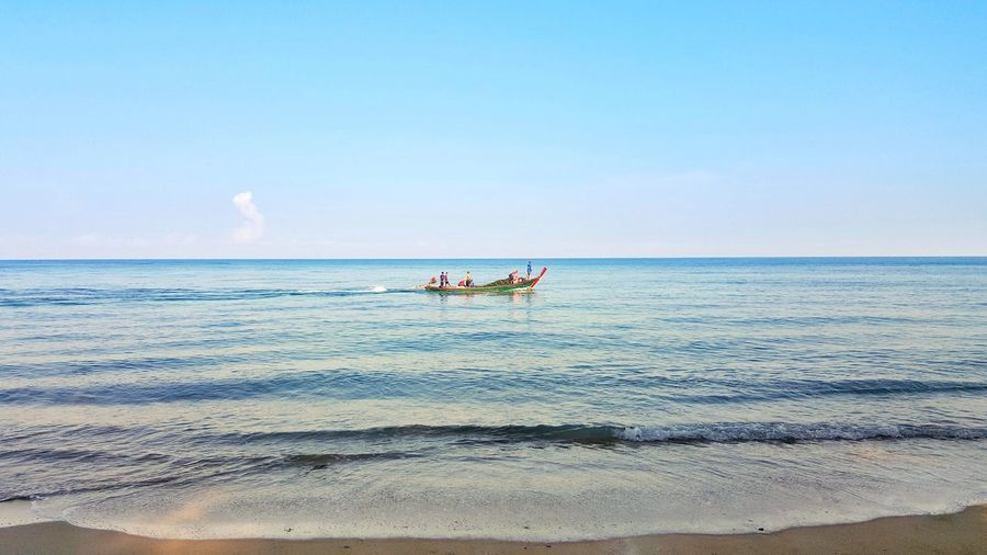 Mid Distance View Of People On Rowboat In Sea Against Sky