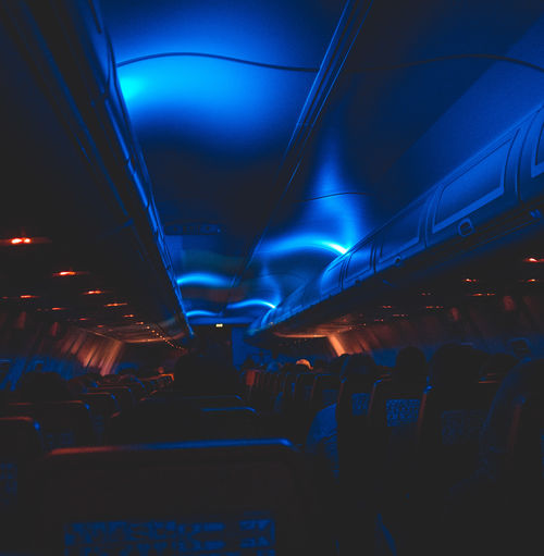 Air Vehicle Airplane Airplane Seat Blue Ceiling Illuminated In A Row Indoors  Lighting Equipment Mode Of Transportation Night No People Public Transportation Seat Transportation Travel Vehicle Interior Vehicle Seat