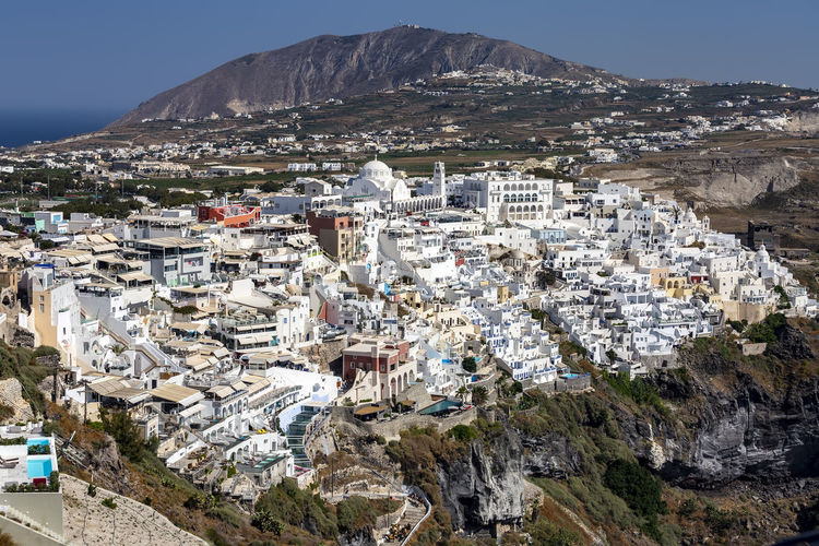 Aerial view of townscape and mountains during sunny day