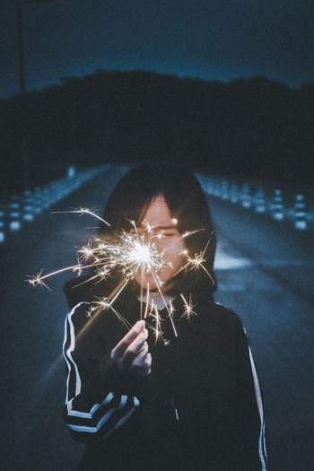Portrait of man holding sparkler at night