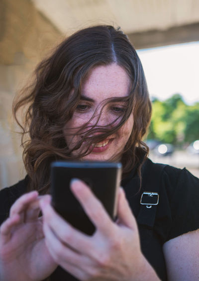 Woman with messy hair in the wind playing with a smartphone. Wireless Technology Technology Communication Smart Phone One Person Mobile Phone Connection Real People Portable Information Device Headshot Lifestyles Front View Using Phone Telephone Holding Portrait Young Adult Young Women Women Hairstyle Outdoors Smile Messy Spontaneous Messy Hair Candid Happiness Happy Laughing The Portraitist - 2019 EyeEm Awards