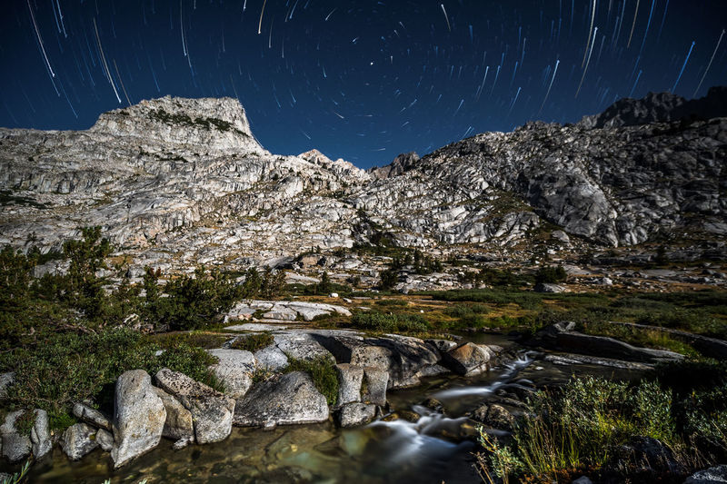 Scenic view of stream amidst rocks against sky at night