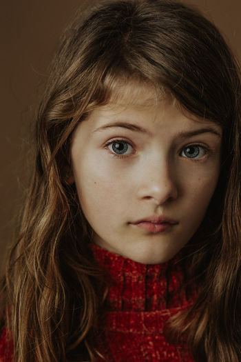 Close-up portrait of serious girl against brown background