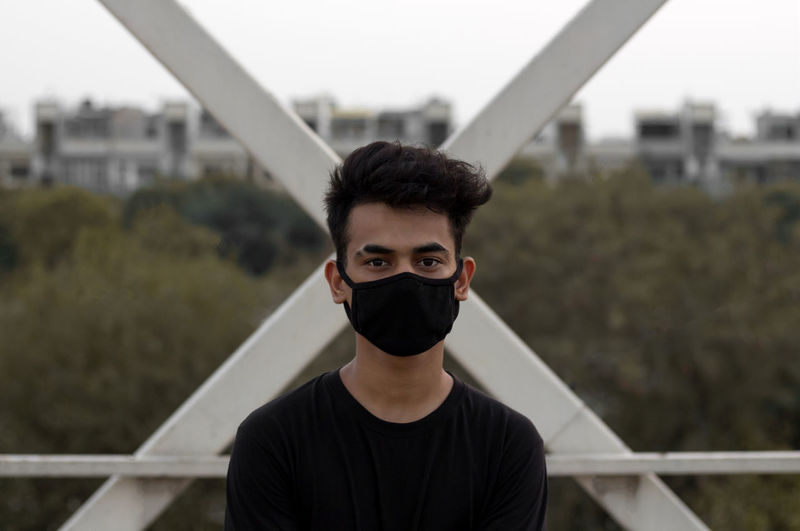 A young male put a mask on to avoid coronavirus infection in a city.