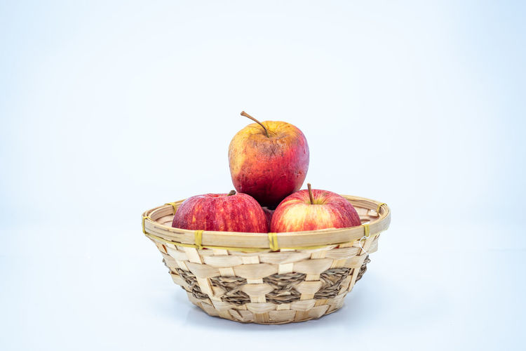 Close-up of apples in basket against white background