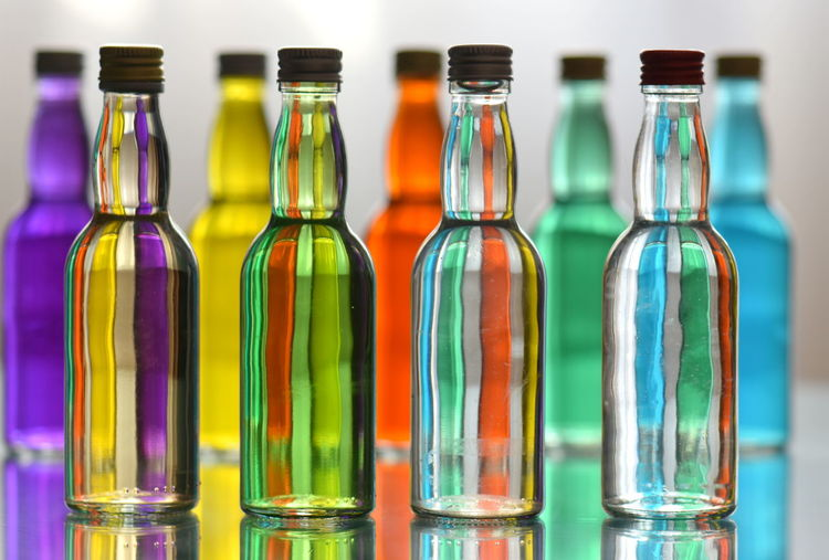 Bottle Container Glass - Material In A Row Group Of Objects Indoors  Transparent No People Alcohol Drinking Glass Glass Multi Colored Food And Drink Refreshment Group Drink Close-up Variation Choice Studio Shot Purity