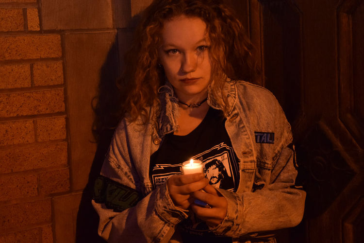 Portrait Of Woman Holding Tea Light Candle At Night