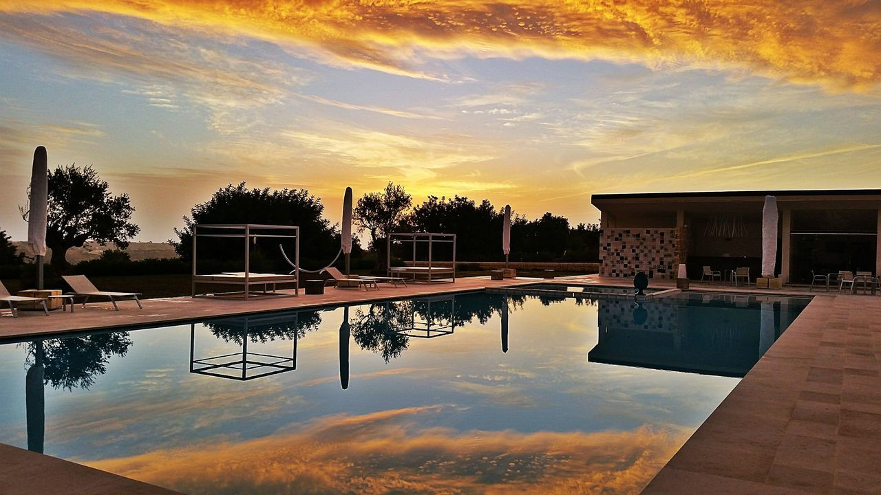 water, swimming pool, reflection, sky, sunset, cloud - sky, built structure, architecture, tree, building exterior, tranquility, outdoors, no people, nature, beauty in nature, day