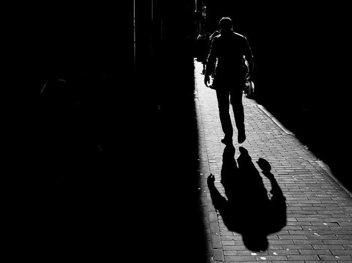 Rear view of silhouette man walking on street