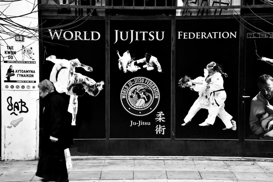 """""""Karate Lady"""" Blackandwhite Photography Old But Awesome Streetphotography Old Woman Elderly EyeEm Gallery Eye4photography  Street Photography From Where I Stand Karate Blackandwhite Wintertime Cold Temperature Warm Clothing High Contrast Building Exterior Poster Billboard Advertising Advertisement Martial Arts Malephotographerofthemonth The Week on EyeEm Graffiti Text Human Representation Outdoors Arts Culture And Entertainment People Adult"""