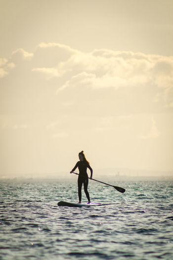 Silhouette man standing in sea against sky