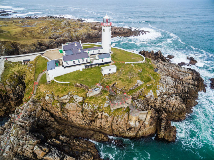 Aerial of the Fanad Head Lighthouse Co. Donegal, Ireland Atlantic Cliffs Donegal Fanad Head Fanad Lighthouse, Donega Helipad Houses Ireland Lighthouse Storm Travel Aerial Aerial View Coast Destination Irish Landmark North Ocean Protection Sea Tourism Tower Warning Waves