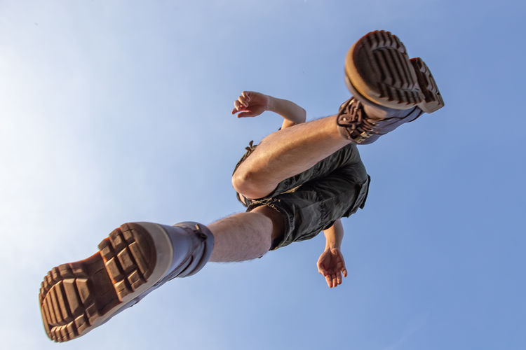 Directly below shot of man jumping against clear sky